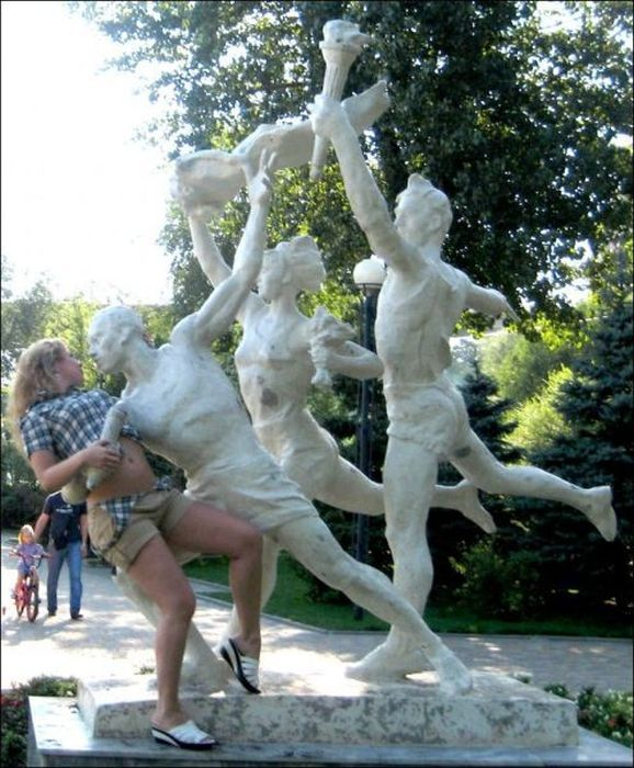 people posing with a statue